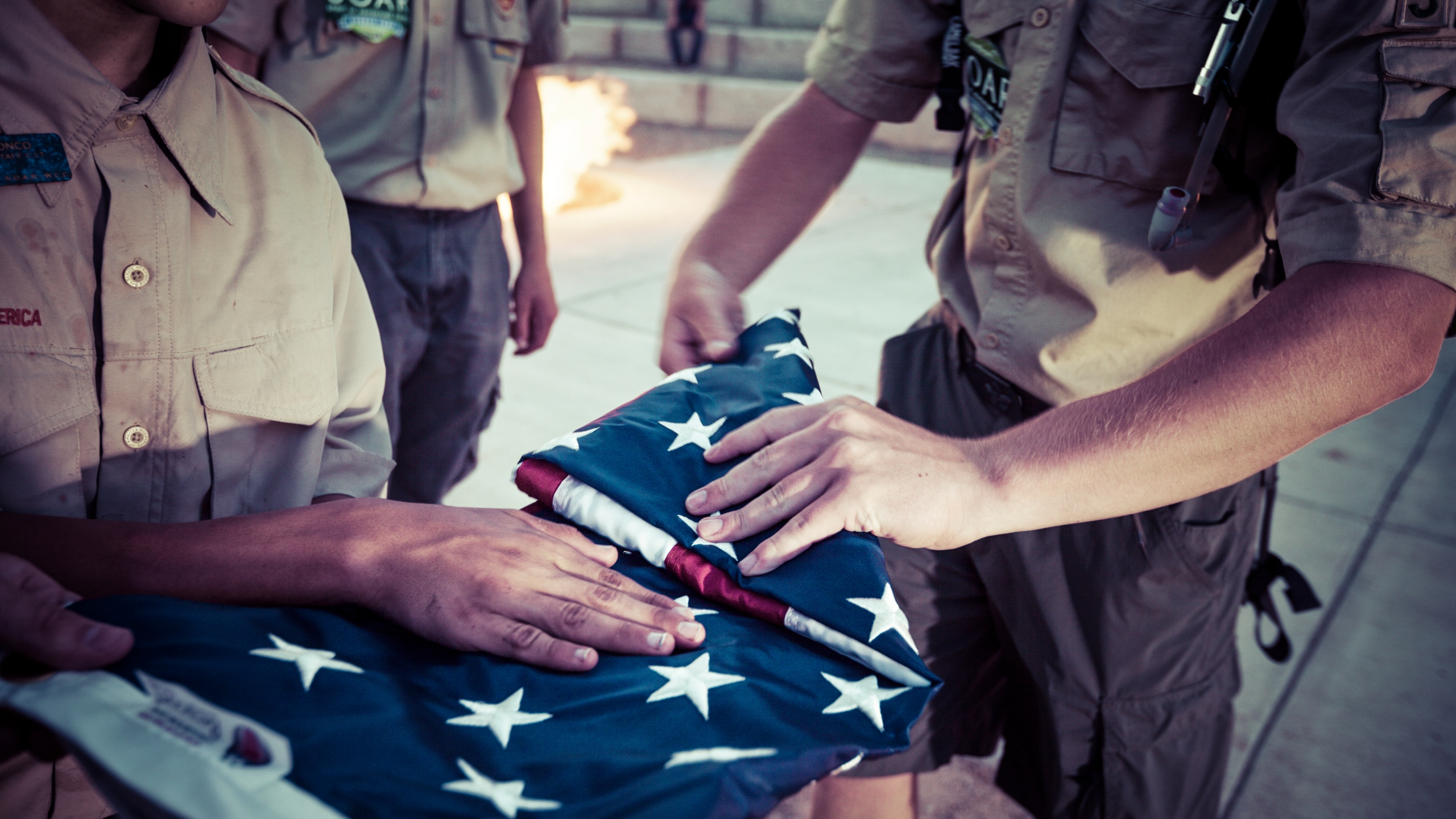 Boy Scouts fold an American flag during ceremony at their camp in Colorado.