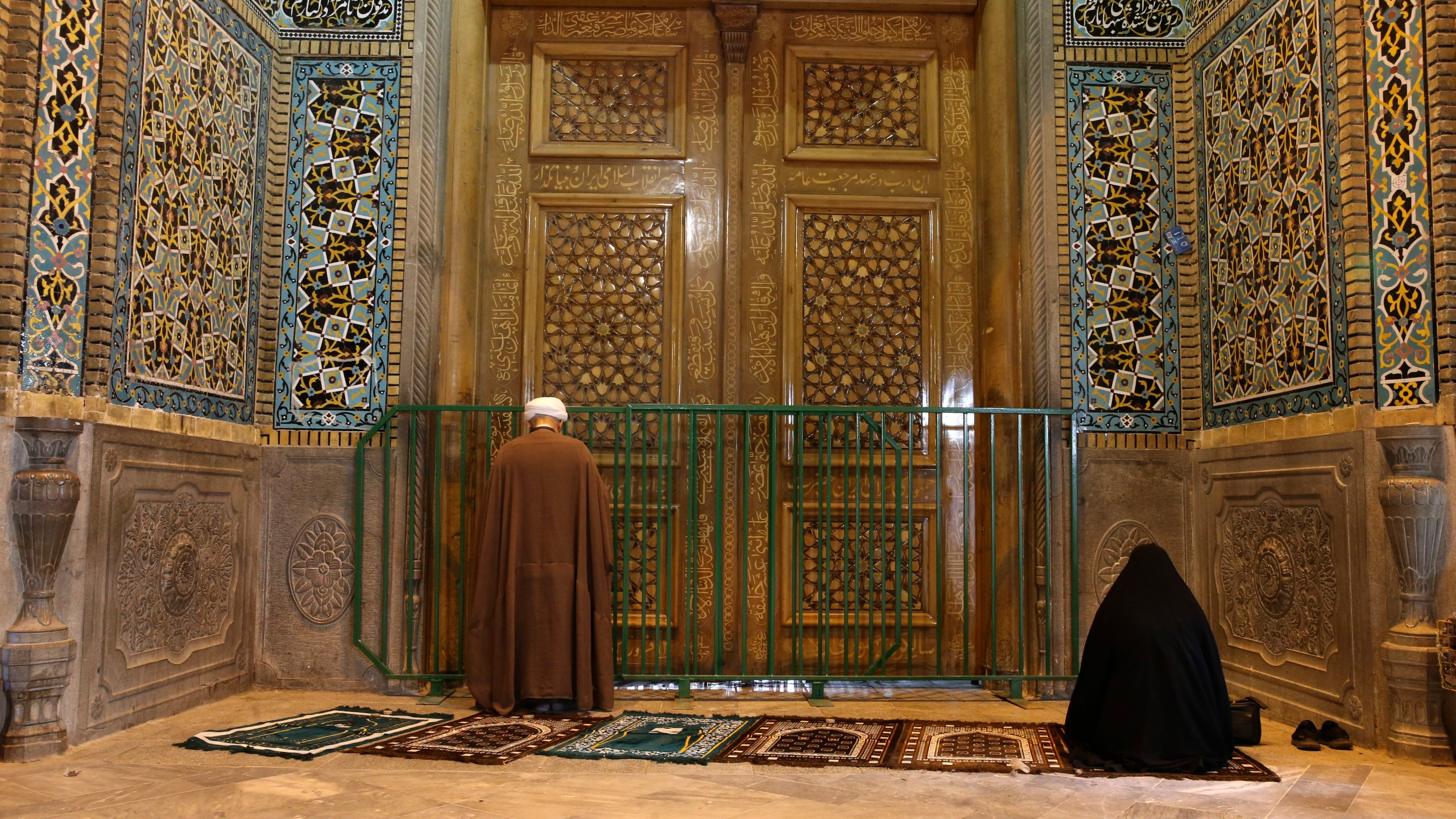 A cleric and a woman pray behind a closed door of Masoume shrine in the city of Qom, some 80 miles south of the capital Tehran, Iran on March 16, 2020. On Monday, Iran closed the Masoume shrine, a major pilgrimage site in the city of Qom, the epicenter of the country's new coronavirus outbreak. Authorities were already restricting access and barring pilgrims from kissing or touching the shrine, but it had remained open. (AP Photo)