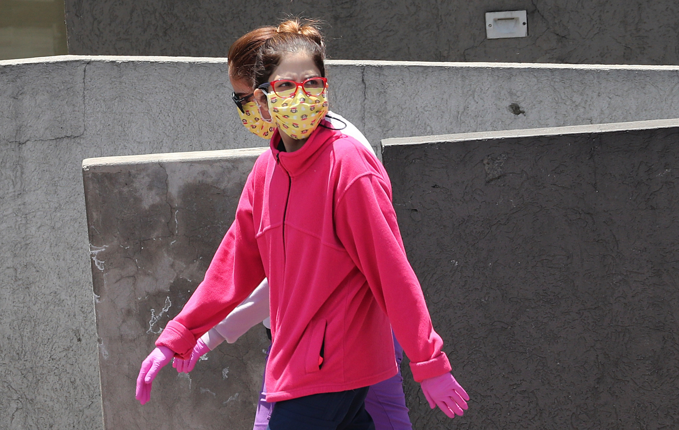 Women wear face masks and gloves as a precaution against the spread of the new coronavirus, in Quito, Ecuador on Thursday. (AP Photo/Dolores Ochoa)