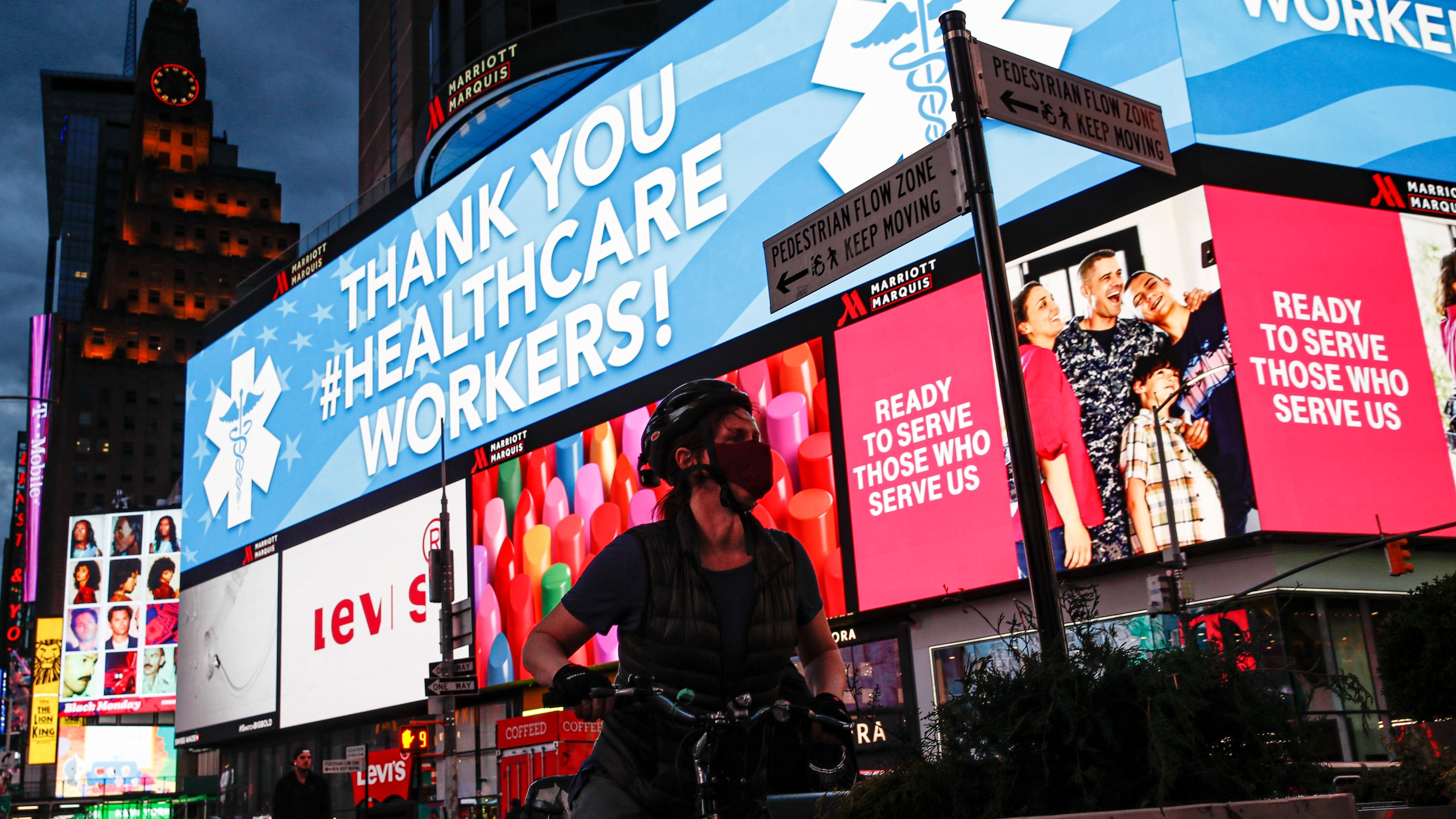 A screen displaying a message thanking healthcare workers due to COVID-19 concerns is displayed in a sparsely populated Times Square, Friday, March 20, 2020, in New York. (AP Photo/John Minchillo)