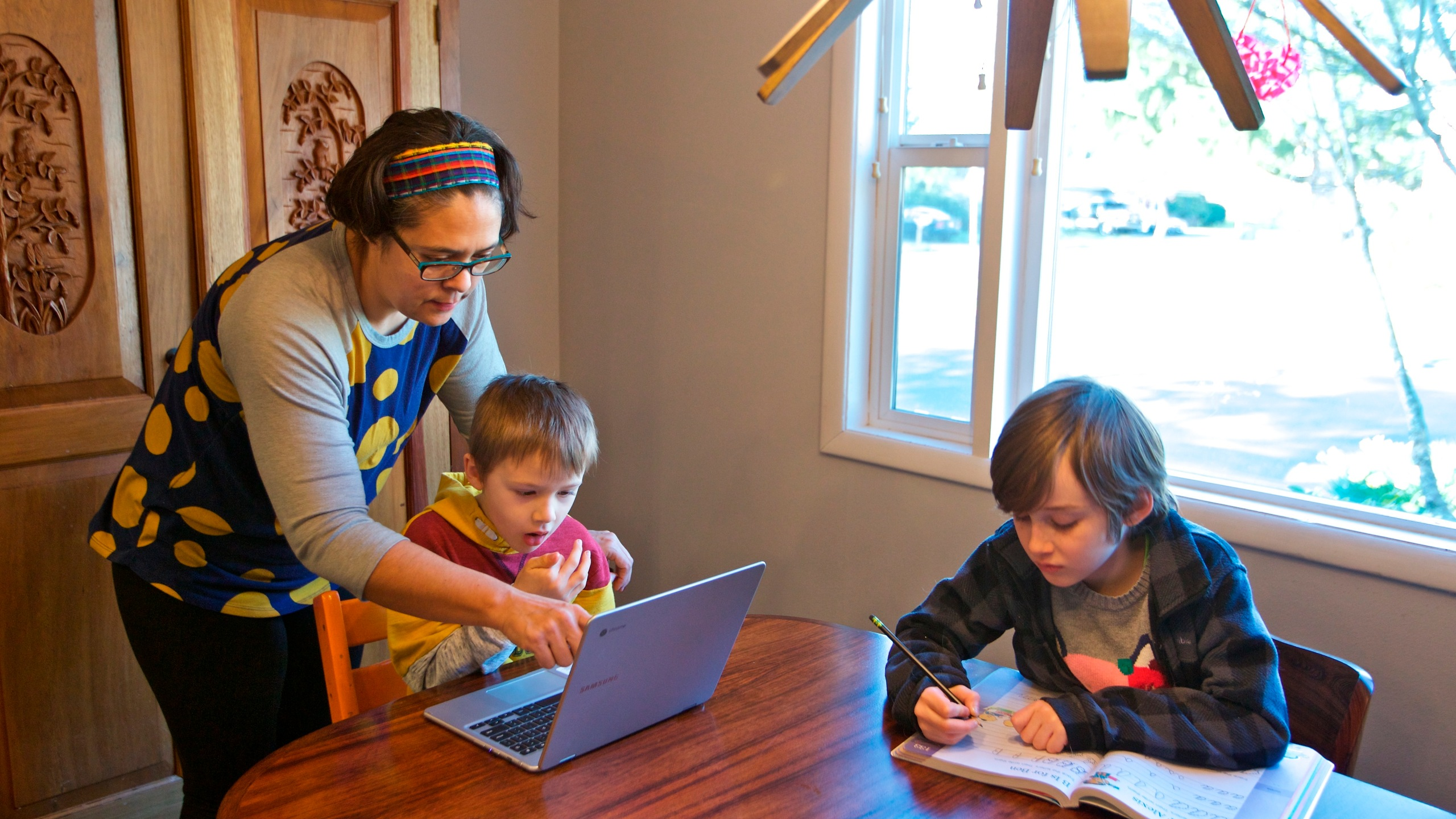 Olivia Bucks, left, helps her son Keith Bucks, center, with an online class assignment while Ashton Morris, right, works on a handwriting lesson from their first grade class at Arco Iris Spanish Immersion School in Beaverton, Ore. Bucks works from home selling books online and now spends her time between working on her business and helping her sons with their school work. They are using her work laptop to access their classroom assignments. (AP Photo/Craig Mitchelldyer)