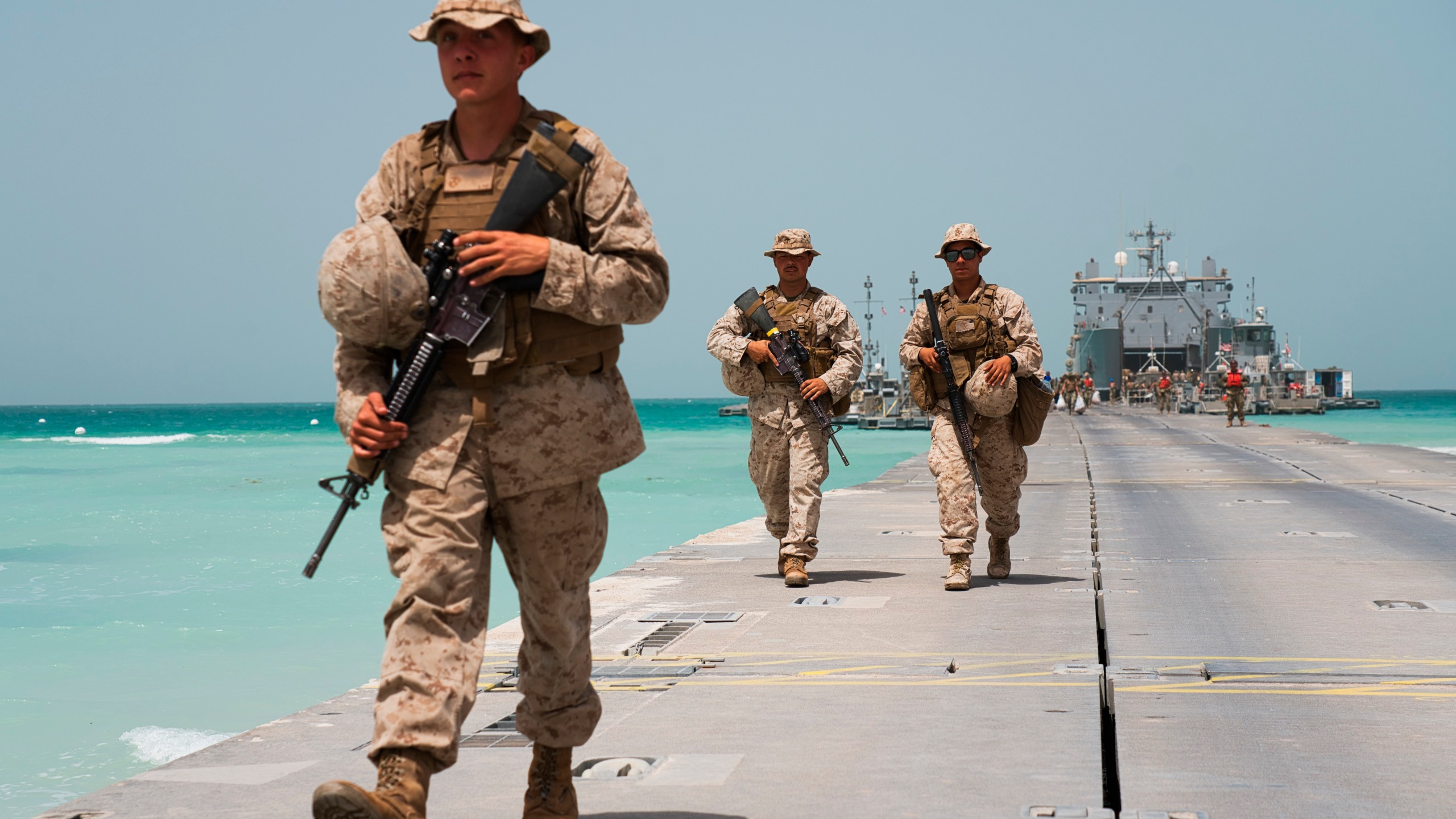 U.S. Marines walk down a removable Trident Pier leading to an American ship docked near an Emirati military base in al-Hamra, United Arab Emirates, Monday, March 23, 2020.The drill on Monday was conducted amid tensions with Iran and despite the global new coronavirus pandemic. (AP Photo/Jon Gambrell)