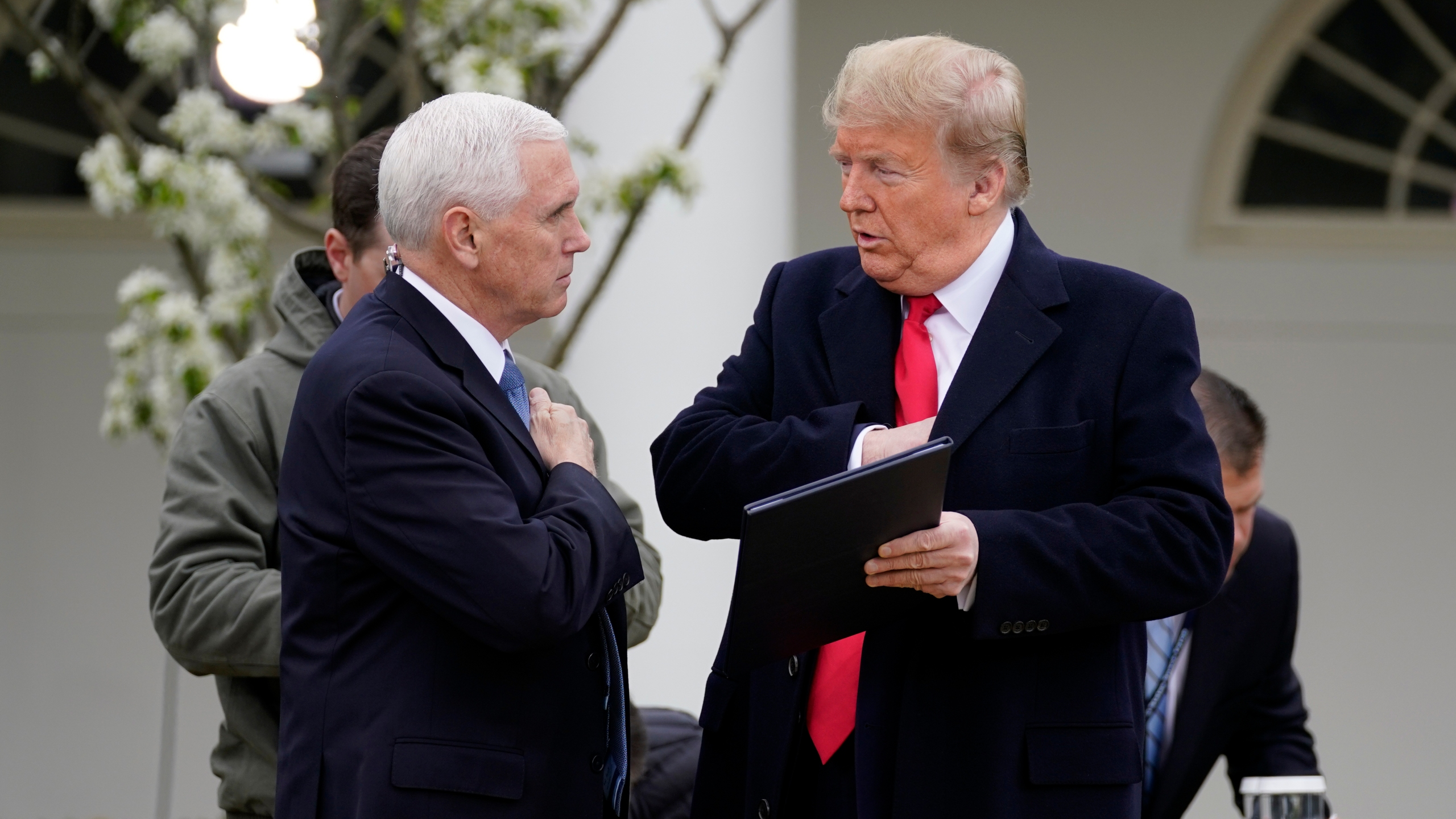 President Donald Trump speaks with Vice President Mike Pence as they arrive for a Fox News Channel virtual town hall, at the White House, Tuesday, March 24, 2020, in Washington. (AP Photo/Evan Vucci)