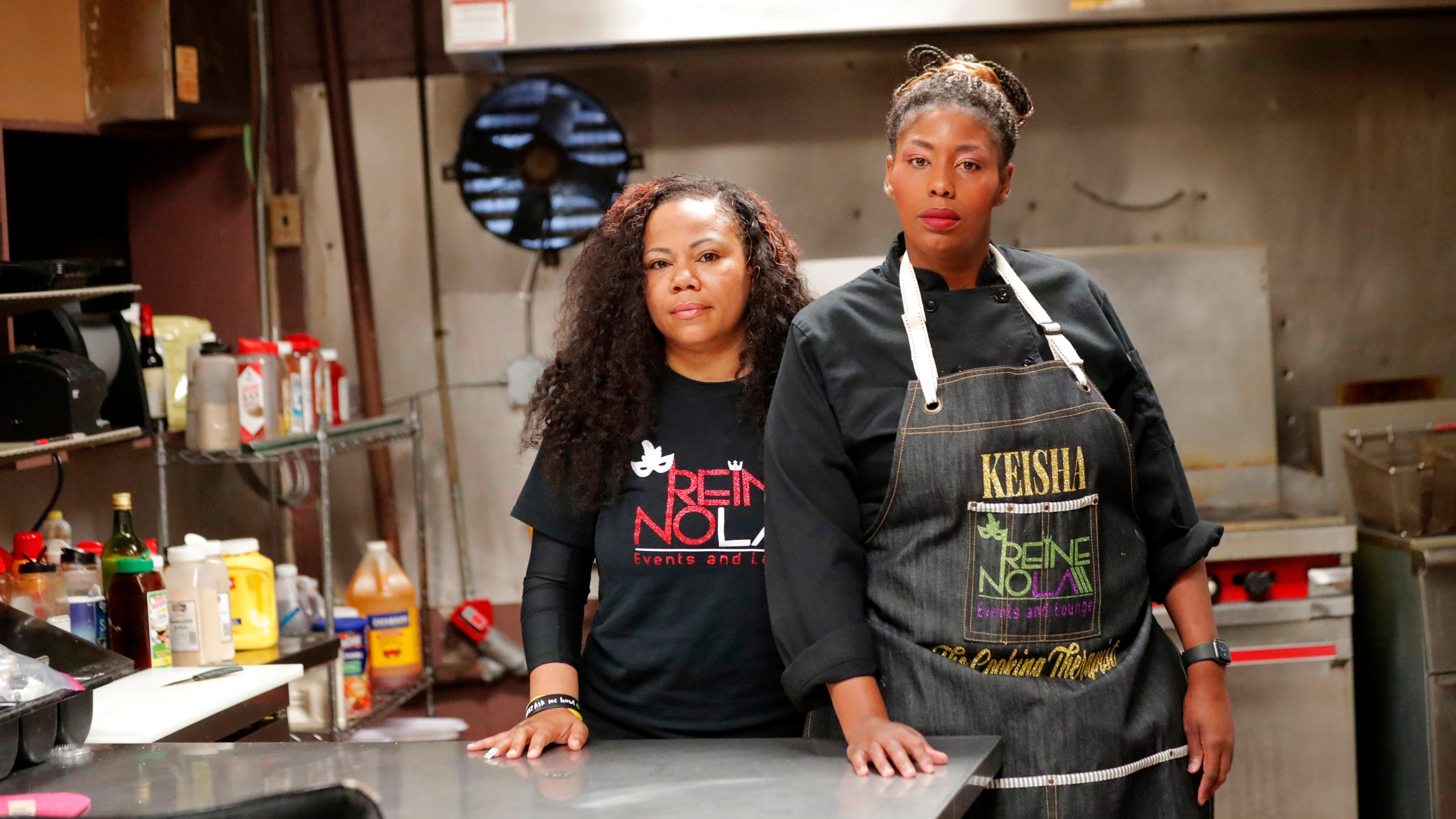 Keisha Henry, right, and her business partner Erica Norwood pose inside their lounge and catering business in New Orleans. Henry said she lost about $10,000 in revenue last week after three big functions she was slated to cater ended up canceling. Meanwhile, she still has expenses related to launching a bar and lounge six months ago. Henry said she regrettably had to lay off several employees. (AP/Gerald Herbert)