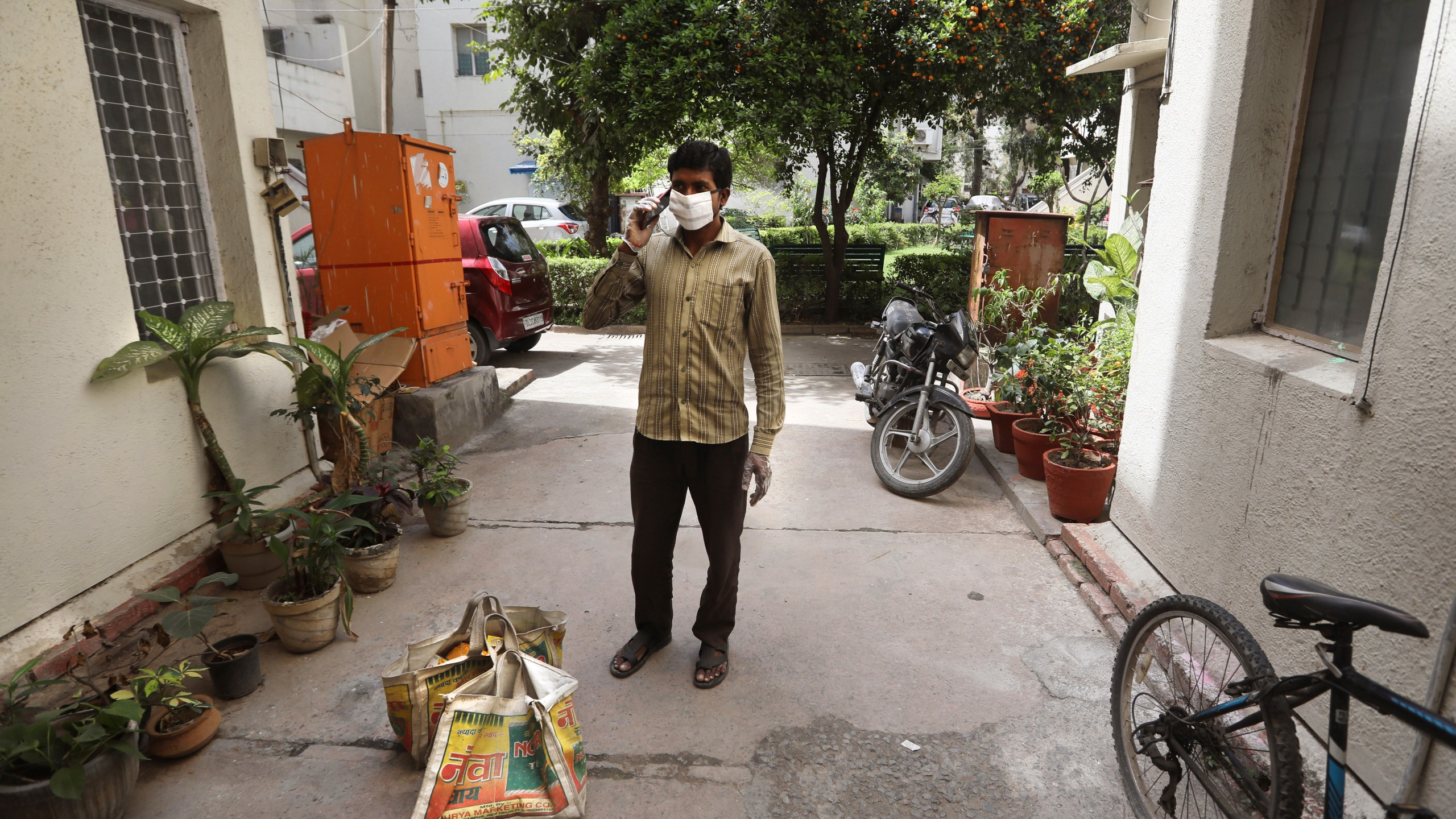 A grocery shop employee, wearing face mask as a precaution against coronavirus, calls a customer living on the second floor to come down to receive their delivery in New Delhi, India, on Wednesday, March 25, 2020. The world's largest democracy went under the world's biggest lockdown Wednesday, with India's 1.3 billion people ordered to stay home in a bid to stop the coronavirus pandemic (AP Photo/Manish Swarup)