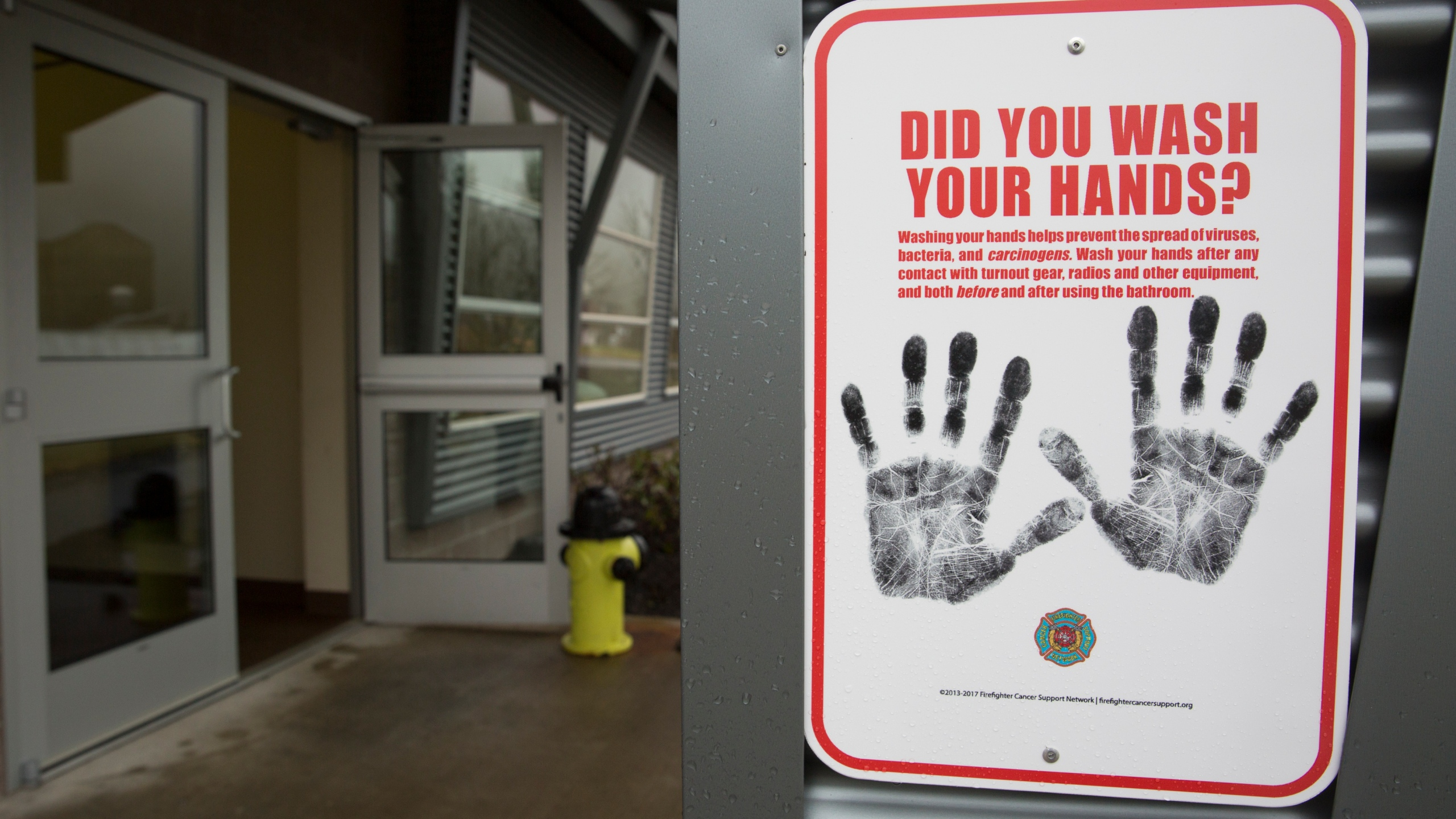 A sign reminding people to wash their hands is pictured outside a dormitory at the Washington State Patrol Fire Training Academy which has been designated as a 2019 novel coronavirus quarantine site for travelers from Hubei Province, China. (Photo by JASON REDMOND/AFP via Getty Images)