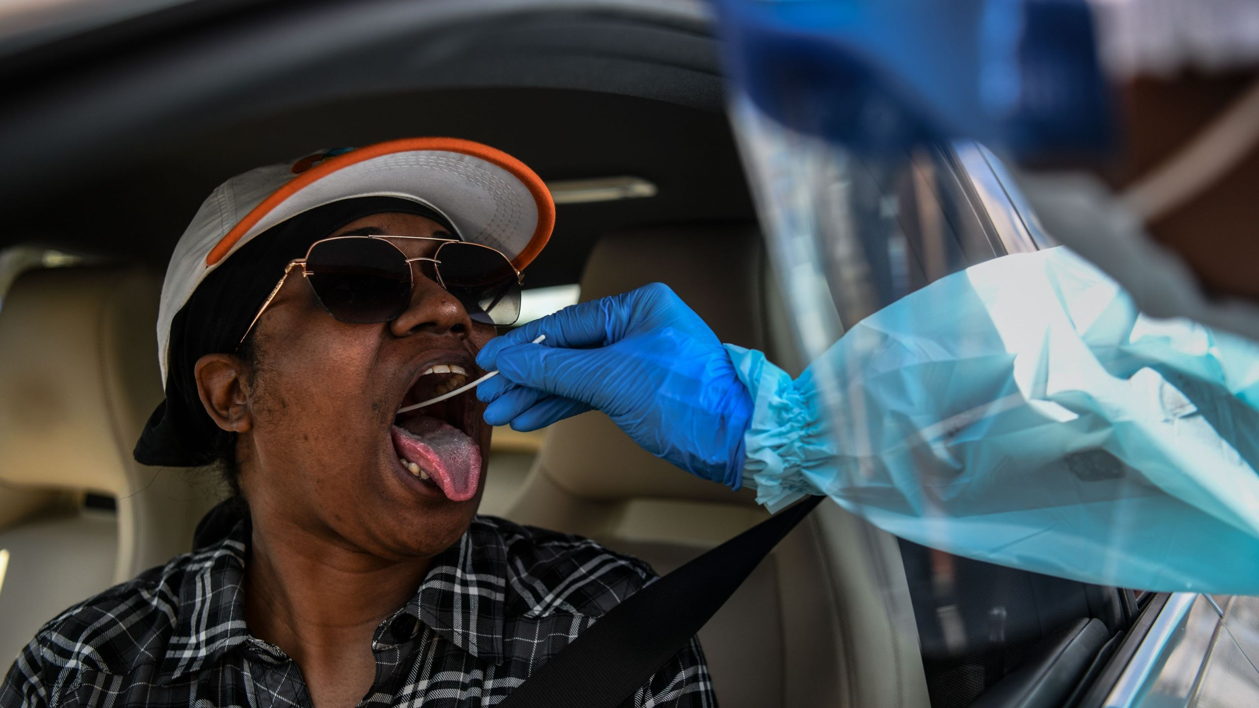 "Medical personnel take samples of Tiffany Natalia at a ""drive-thru"" coronavirus testing lab set up by a local community center in West Palm Beach 75 miles north of Miami (Photo by CHANDAN KHANNA/AFP via Getty Images)"