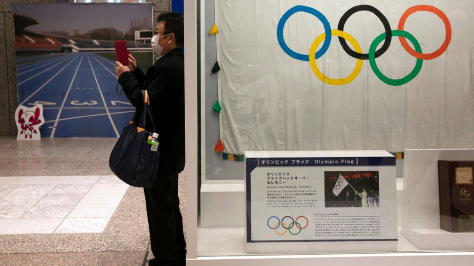 A man wearing a mask takes pictures of the mascots for the Tokyo 2020 Olympics and Paralympics in Tokyo. (AP Photo/Jae C. Hong, File)