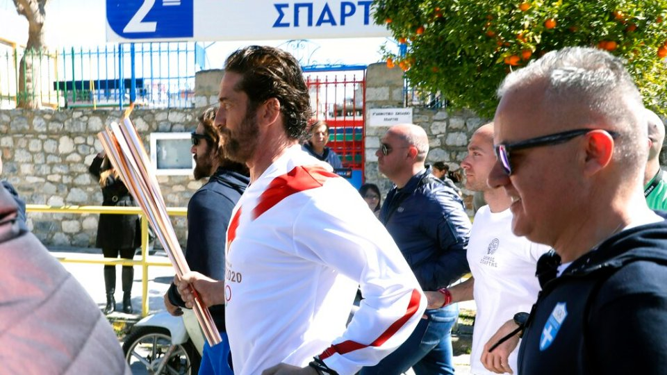 """US actor Gerard Butler runs as a torchbearer during the Olympic torch relay of the 2020 Tokyo Olympic Games in the southern Greek town of Sparta, Friday, March 13, 2020. Greece's Olympic committee says it is suspending the rest of its torch relay for the Olympic flame due to the """"unexpectedly large crowd"""" that gathered to watch despite repeated requests for the public to stay away to prevent the spread of the new coronavirus. (AP Photo)"""