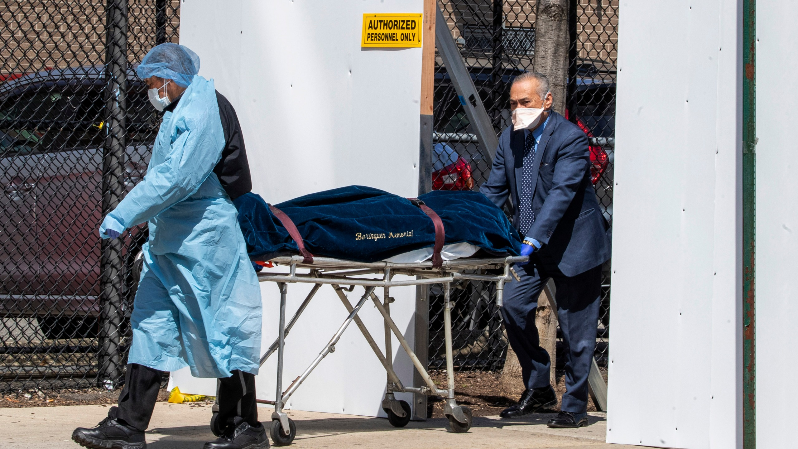 A funeral director and a Wycoff Heights Medical Center, employee transport a body, Wednesday, April 1, 2020, in New York. (AP Photo/Mary Altaffer)