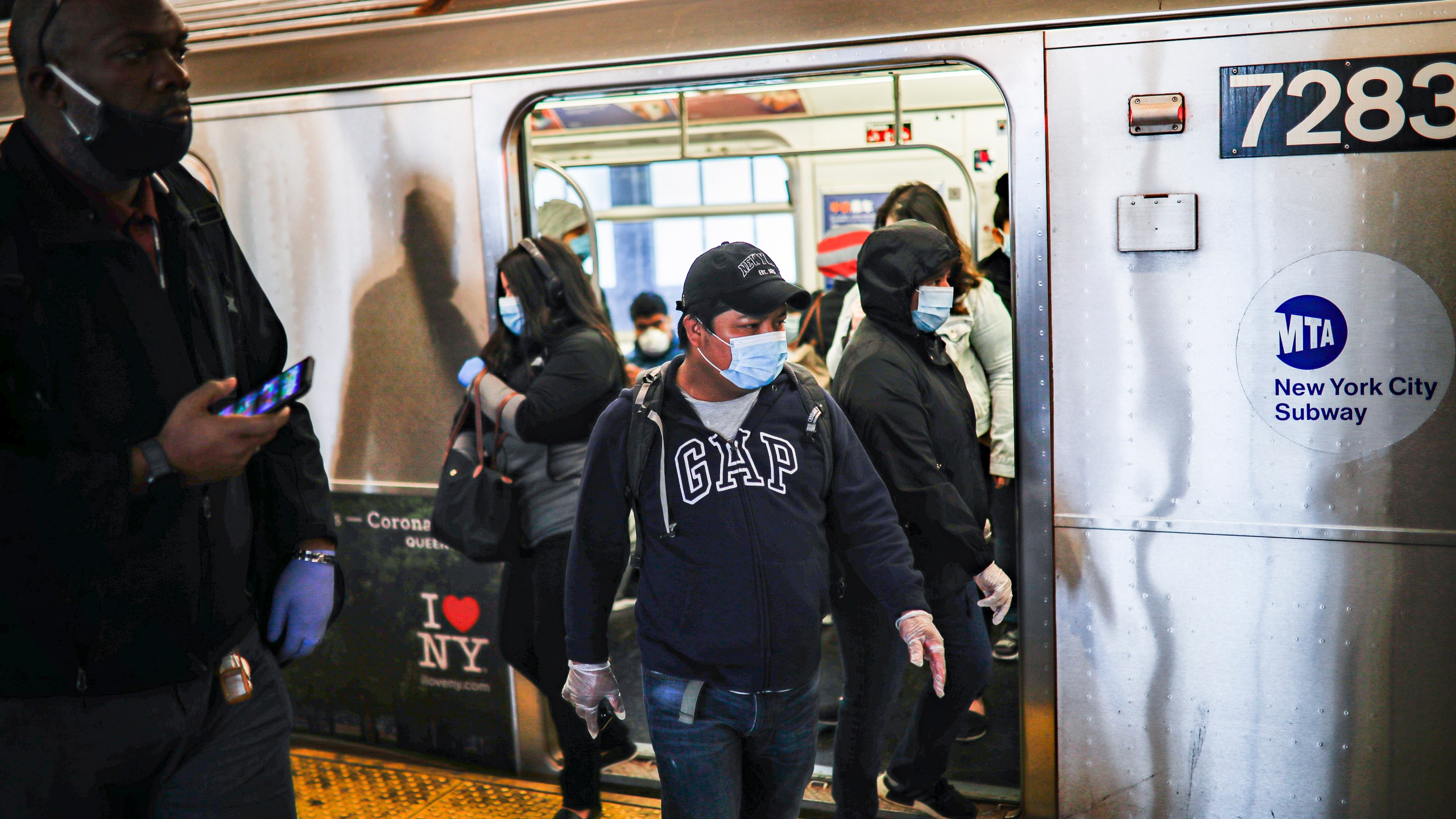 Subway riders, wearing personal protective equipment due to COVID-19 concerns, step off a train in New York. (AP Photo/John Minchillo)
