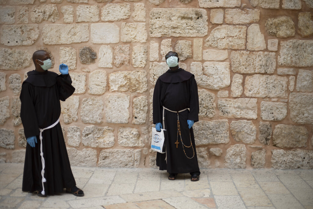 Priests wait to enter the Church of the Holy Sepulchre, a place where Christians believe Jesus Christ was buried, during Holy Thursday in Jerusalem's Old City. The traditional Holy Thursday procession took place inside the church without public attendance this year. (AP Photo/Ariel Schalit)