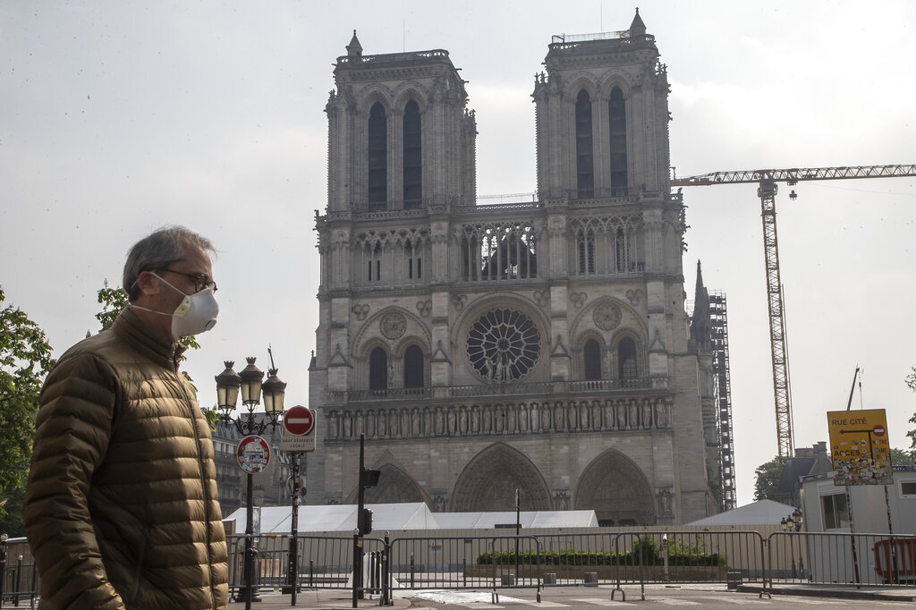 A man wears a mask to protect against the spread of the coronavirus as he walks past the Notre Dame cathedral in Paris on Monday. The reconstruction of the fire-devastated Notre Dame Cathedral a year ago on April 15, 2019, was suspended last month due to the coronavirus pandemic. (AP Photo/Michel Euler)