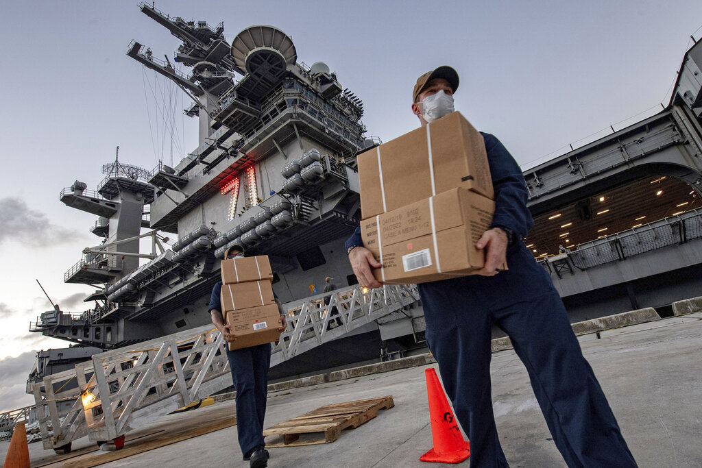 Sailors assigned to the aircraft carrier USS Theodore Roosevelt move ready to eat meals for sailors who have tested negative for COVID-19 and are being taken to local hotels in an effort to implement social distancing at Naval Base Guam.(Mass Communication Specialist Julio Rivera/U.S. Navy via AP)