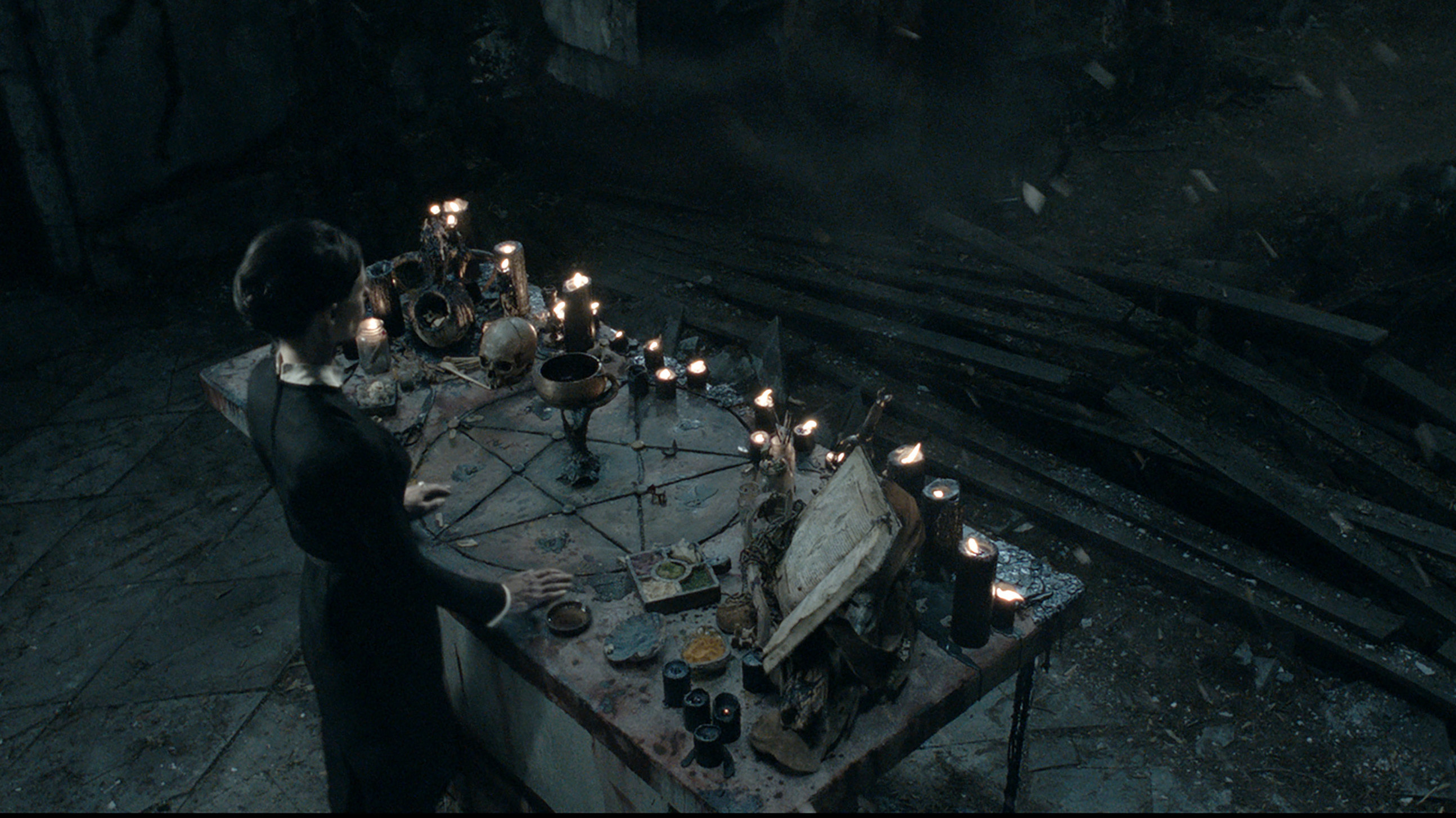 The Occultist, as she's called in the film, stands before her altar. Her aesthetic is very clearly witchy dark academia.